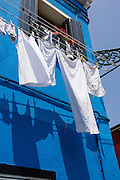 """White laundry drying outdoors casts shadows onto blue house. Burano, known for knitted lacework, fishing, and colorfully painted houses, is a small archipelago of four islands linked by bridges in the Venetian Lagoon, in the Veneto region of Italy, Europe. Burano's traditional house colors are strictly regulated by government. The Romans may have been first to settle Burano. Romantic Venice (Venezia), """"City of Canals,"""" stretches across 100+ small islands in the marshy Venetian Lagoon along the Adriatic Sea in northeast Italy, between the mouths of the Po and Piave Rivers. Venice and the Venetian Lagoon are honored on UNESCO's World Heritage List."""