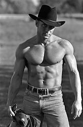 shirtless muscular cowboy in jeans and a cowboy hat on a ranch