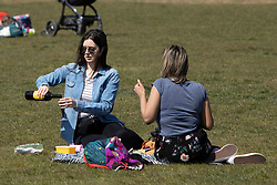 © Licensed to London News Pictures. 24/04/2021. London, UK. A woman pours a glass of red wine during sunny weather in Greenwich Park in south east London. Temperatures are expected to rise with highs of 16 degrees forecasted for parts of London and South East England today . Photo credit: George Cracknell Wright/LNP