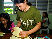 29 JANUARY 2018 - MALILIPOT, ALBAY, PHILIPPINES: Women in a shelter make face masks to protect themselves and their families from volcanic ash. They live on the slopes of Mayon volcano and were evacuated when the volcano started erupting. Mayon volcano's eruptions continued Monday. At last count, more 80,000 people have been evacuated from their homes of the slopes of the volcano and are crowded into shelters in communities outside of the danger zone.    PHOTO BY JACK KURTZ