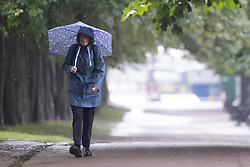© Licensed to London News Pictures. 07/08/2021. London, UK. A woman uses an umbrella to shelter from heavy rain in Greenwich Park in South East London. A yellow weather warning for thunderstorms is in place for parts of England. Photo credit: George Cracknell Wright/LNP