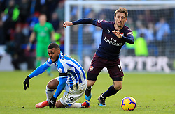 Huddersfield Town's Elias Kachunga (left) and Arsenal's Nacho Monreal battle for the ball during the Premier League match at the John Smith's Stadium, Huddersfield.