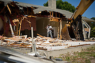 Xavier Mascareñas/Treasure Coast Newspapers; Gary Tompkins, of Fort Pierce, a laborer with John O'Connell Inc., sorts debris during the demolition of the house where Tyler Hadley and his family lived on Granduer Avenue in Port St. Lucie on Tuesday, April 14, 2015. Hadley killed his parents in the home in 2011. Demolition company owner John O'Connell said once the house is removed, including the cement slab, the ground will be graded and covered with seed and straw.
