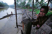 A young Asmattan child in the village of Komor, along the Bo River, Irian Jaya, Indonesia. The Asmat is the worlds's largest (and hottest), swamp. (Man Eating Bugs page 64,65)