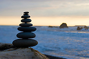 Stacked rocks on driftwood with a sunset view of coastal surf