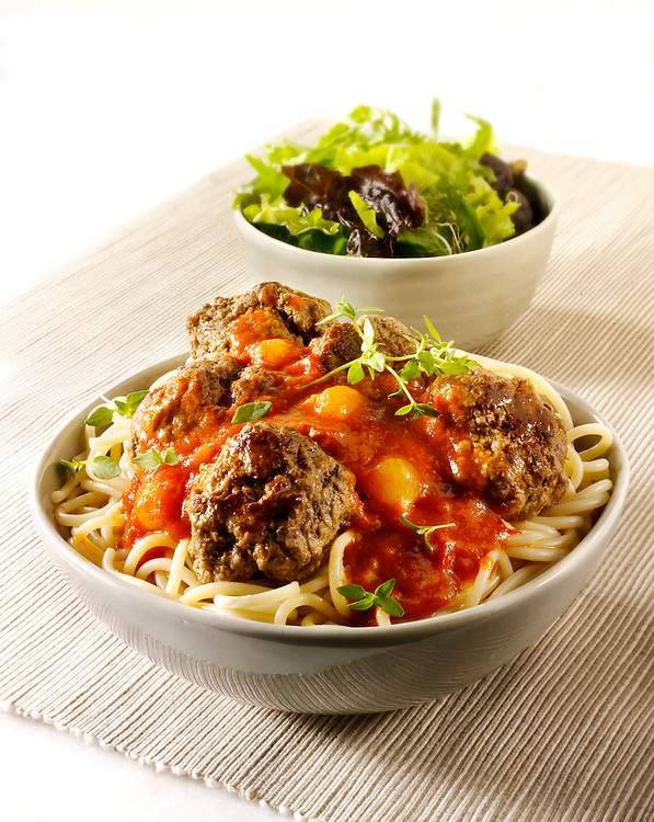 Meat Balls on spghetti with a tomato, basil & shalott sauce with a green salad in a table setting.