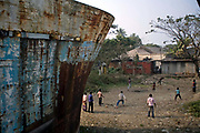 Boys play cricket in the shadow of a rusty hull of a ship in the docks at Sadarghat, Chittagong, Bangladesh