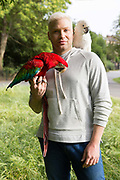 Ioannis Tsangaris with Snowy the Umbrella Cockatoo and Manolo the green winged Macaw in Brockwell Park on the 23rd June 2018 in Herne Hill in the United Kingdom. Ioannis belongs to a large parrot keepers community.