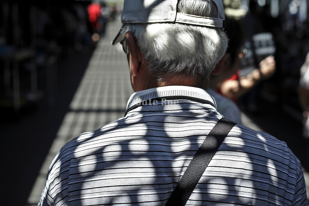 silver haired senior man with strong sun shadow projection of overhead grill