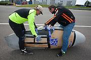 Jan van Steeg stapt in de Cygnus, de fiets wordt nog beschermd tegen valschade met karton. Het Nederlandse team van Cygnus test op de testbaan van de RDW in Lelystad de fiets waarmee ze een record willen gaan rijden.<br /> <br /> Jan van Steeg is getting in the Cygnus. The bike is still protected against damages with cardboard. Team Cygnus is testing their bike to break the world record at the test track in Lelystad.