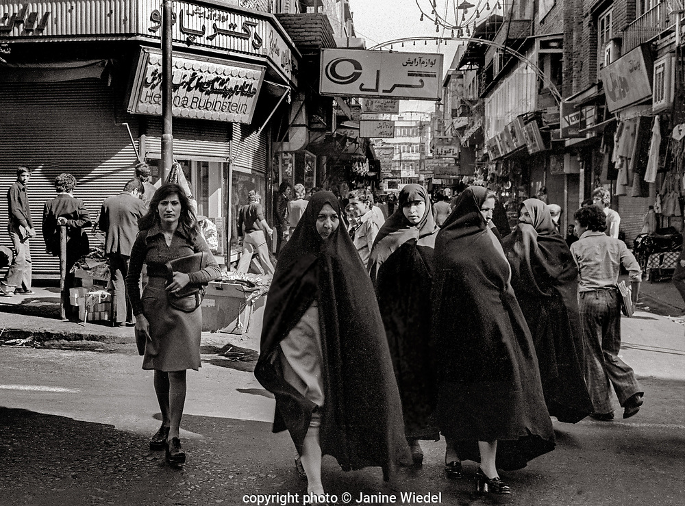 Group of women in chadors ( hijabs ) in Tehran street with Western boutiques in background.