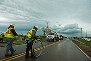 Oklahoma, USA. May 21, 2013. Electrical crews roll up downed powerlines as another storm approaches.