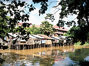 Ramshackle houses behind tourist hotels on the Siem Reap River.