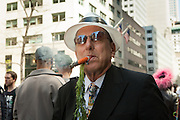 A man smokes a cigar disguised as a carrot, complete with the greens.