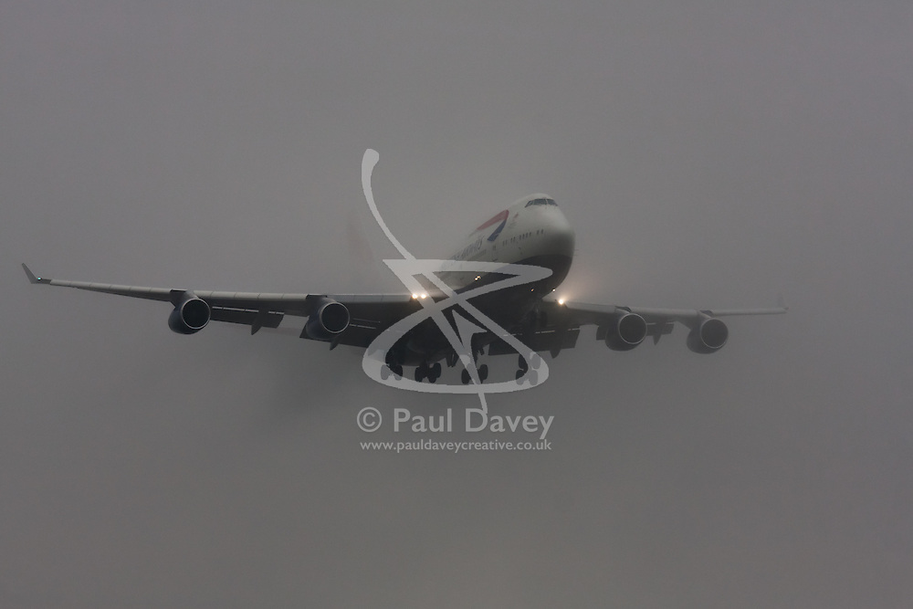 """January 3rd 2015, Heathrow Airport, London. Low cloud and rain provide ideal conditions to observe wake vortexes and """"fluffing"""" as moisture condenses over the wings of landing aircraft. With the runway visible only at the last minute, several planes had to perform a """"go-round"""", abandoning their first attempts to land. PICTURED: A British Airways Boeing 747 Jumbo Jet emerges from the low cloud moments before touchdown on Heathrow's runway 27L."""