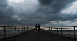 © Licensed to London News Pictures. <br /> 08/06/2014. <br /> <br /> Saltburn, United Kingdom<br /> <br /> A couple walk along the pier as dark and brooding thunder clouds form over Saltburn, Cleveland.<br /> <br /> Photo credit : Ian Forsyth/LNP