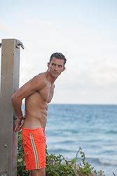 sexy man in an outdoor shower at the beach