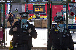 © Licensed to London News Pictures.19/03/2021. London,UK. Two police officers walk past the Covid-19 sign in Stratford, east London during the third national lockdown to prevent the spread of coronavirus. Lockdown restrictions are being relaxed over the coming weeks, following a significant drop in infections and deaths. Photo credit: Marcin Nowak/LNP