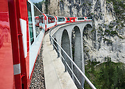 """Landwasser Viaduct & tunnel. Playfully, Switzerland advertises the Glacier Express as """"the slowest express train in the world."""" Opened in 1930, this narrow gauge railway connects the mountain resorts of Zermatt and St. Moritz in the Swiss Alps, from the Matterhorn to Piz Bernina, frequently applying a rack-and-pinion system to go up and down steep grades. An especially curlycue portion of the Glacier Express route is honored as a UNESCO World Heritage Site: the """"Rhaetian Railway in the Albula / Bernina Landscapes"""". Jointly operated by the Matterhorn Gotthard Bahn (MGB) and Rhaetian Railway (RhB), the 7.5 hour railway journey crosses 291 bridges, enters 91 tunnels and reaches 2033 m (6670 ft) elevation at Oberalp Pass."""