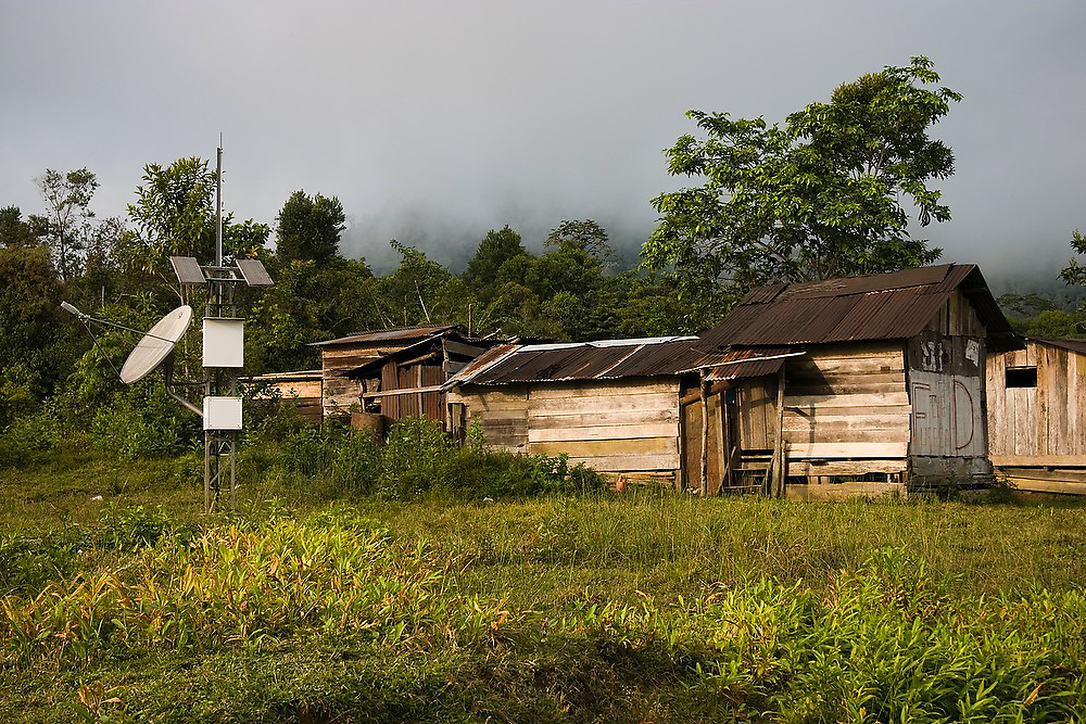 Wooden houses with a satellite dish at a coca farm in the upper valley of the Madre de Dios River in the Peruvian Amazon.