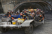 """Emerging from the portal after a 10-hour shift, a dozen of coal miner Todd Kincer's colleagues lounge on the """"man car"""" that transports them to and from the coal face, several miles into the mountain, at the Advantage One Mine outside Whitesburg, Kentucky. (From the book What I Eat: Around the World in 80 Diets.)"""