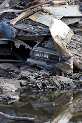 30 Sept, 2005.  New Orleans, Louisiana. Lower 9th ward. Hurricane Katrina aftermath. <br /> The remnants of the lives of ordinary folks, now covered in mud as the flood waters remain. A car's headlights peer out from underneath a pile of rubble.<br /> Photo; ©Charlie Varley/varleypix.com