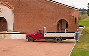 The winery building and a man loading a truck. Bodega Bouza Winery, Canelones, Montevideo, Uruguay, South America