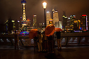 People shelter under umbrellas to view the skyline of Lujiazui Shanghai, China