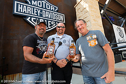 Sturgis Chief of Police Geody Vandewater with Jesse James Dupree, lead vocalist of Jackyl (and part of the Full Throttle Saloon and Jesse James Bourbon) and Michael Ballard of the Full Throttle Saloon as they did a bottle signing with their new spirits at the Harley-Davidson Rally Point on the corner of Main and Harley-Davidson Way during the Sturgis Black Hills Motorcycle Rally. SD, USA. Saturday, August 10, 2019. Photography ©2019 Michael Lichter.