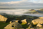 Gritstone boulders and evidence of the millstone industry of old overlook Curbar village and a misty Derwent Valley. A termperature inversion at sunrise in the Derbyshire Peak District, England, UK.