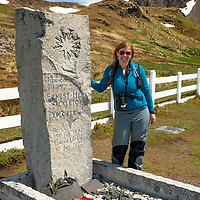 Naturalist Karen Velas poses by Sir Ernest Henry Shackleton's grave. Shackleton's grave is in the cemetery near the old whaling station at Grytviken on the north coast of South Georgia Island.