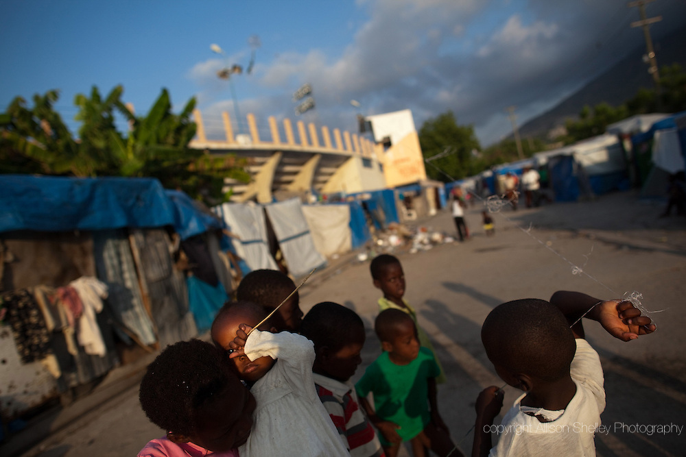 Kids fly kites at a tent camp in the parking lot of Sylvio Cator soccer stadium in downtown Port-au-Prince, Haiti, April 8, 2011.  Camp residents are being evicted from the grounds so that the stadium can again be fully utilized.