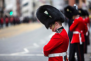 A member of the Queens guard bows his head as the coffin of baroness thatcher passes along Fleet Street on route to St. Paul's cathedral where her funeral took place. 17th April 2013. London, United Kingdom.