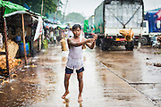 13 JUNE 2013 - YANGON, MYANMAR:  A worker tosses coconuts to a coworker during a monsoon rain storm in Yangon. Yangon, formerly Rangoon, is Myanmar's commercial capital and used to be the national capital. The city is on the Irrawaddy River and has a vibrant riverfront.   PHOTO BY JACK KURTZ