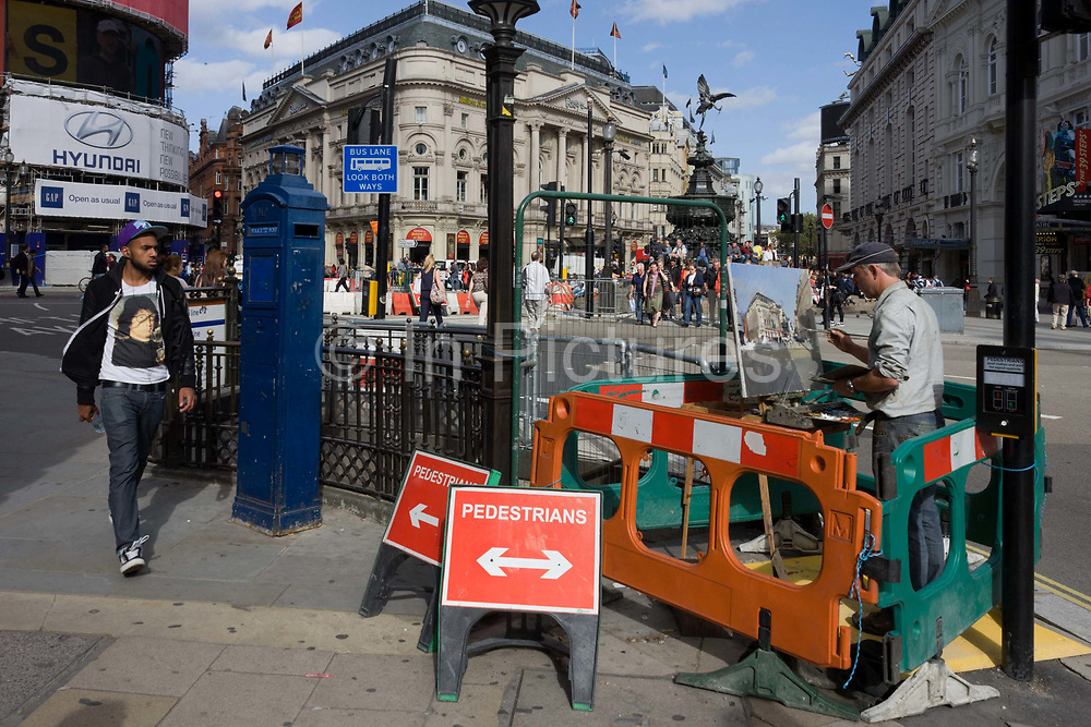 """An artist is incongruously enclosed in roadworks barriers at the busy junction of Piccadilly Circus in London's West End. Painting with an easel and applying careful brush strokes amid the noise and chaos of this busy traffic junction in the capital. A young man walks past barely noticing the artist as he strides through the heart of London's west end. But on the youth's t-shirt is a modern interpretation (wearing glasses and apparently spitting liquid into a cup) of Hans Memling's """"Portrait of a Man with a Coin of the Emperor Nero (Bernardo Bembo)"""" German-born artist Jan van Mimnelinghe (Hans Memling, c. 1435-94) was well known all over Europe. During his lifetime, he painted commissions not only for the Burgundian Dukes, but also for patrons in Germany, Austria, Venice, Florence and London."""