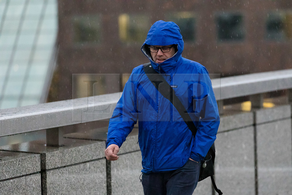 © Licensed to London News Pictures. 01/12/2018. London, UK.  A man walking across London Bridge this morning during rain and wet weather on the first day of meteorological winter.  Photo credit: Vickie Flores/LNP