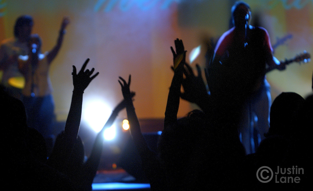 Young men and women are seen praying during Friday night services for college-age Christians at New Life Church in Colorado Springs, CO on July 8, 2005. The services are held by one of the church's youth ministries, called The Mill, and feature religous rock music, sophisticated lighting, and intense prayer.