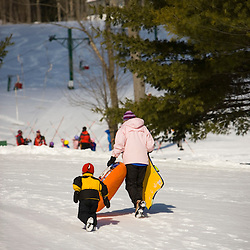 A woman and her young son climb a sledding hill in Quechee, Vermont. Model Release.