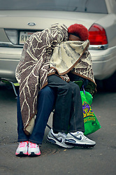 04 March 2014. New Orleans, Louisiana.<br /> Fat Tuesday. Mardi Gras Day. Revelers wrap up warm against the cold and rain as they await the early morning Krewe of Zulu parade.<br /> Photo; Charlie Varley/varleypix.com