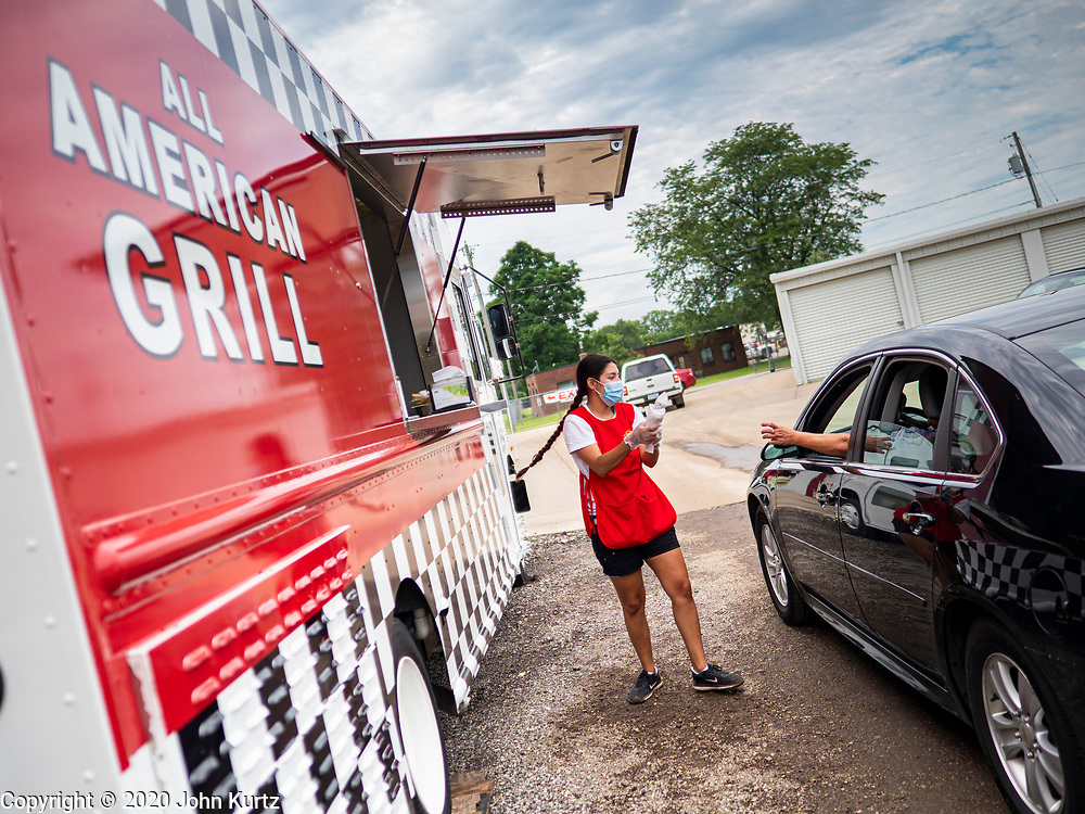 """26 JUNE 2020 - DES MOINES, IOWA: NADINE GARCIA, a worker at the American Grill trailer, delivers corn dogs to a customer at Fair Food Friday in Des Moines. The 2020 Iowa State Fair, like many state fairs in the Midwest, has been cancelled this year because of the COVID-19 (Coronavirus) pandemic. The cancellation of the fair left many small vendors stranded with no income. Some of the fair food vendors in Iowa started """"Fair Food Fridays"""" on a property a few miles south of the State Fairgrounds. People drive up and don't leave their cars while vendors bring them the usual midway fare; corndogs, fried tenderloin sandwiches, turkey legs, deep fried Oreos, lemonaide and smoothies. Fair Food Friday has been very successful. The vendors serve 450-500 people per Friday and during the lunch rush people wait in line in their cars 30 - 45 minutes to place an order.     PHOTO BY JACK KURTZ"""