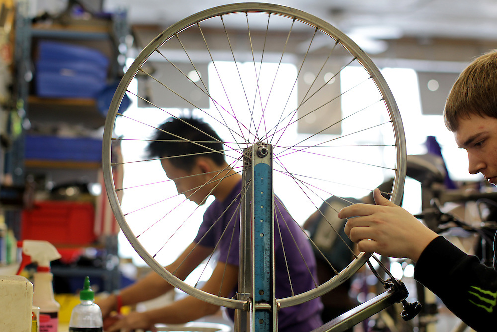 Youth Express apprentices Marcus Wachholz, 17, right, and Koua Yang, 15, work to straighten wheels on donated bikes at Express Bike Shop in St. Paul, Minnesota.  By refurbishing and selling bicycles, youth apprentices learn mechanical, business, and entrepreneurial skills..