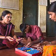 CAPTION: Mobility India's Sudhamani R. trains Drakshayani in the skills she'll need as an After-School Club (ASC) Coordinator. LOCATION: Handrakalli Mole (village), Kasaba (hobli), Chamrajnagar (district), Karnataka (state), India. INDIVIDUAL(S) PHOTOGRAPHED: From left to right: Sudhamani R., Chinnu and Drakshayani.