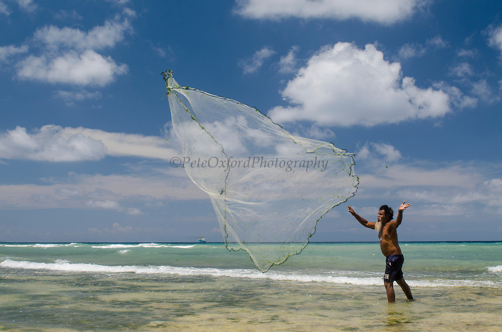 Local Papuan Cast Net fisherman<br /> Biak Island<br /> West Papua<br /> Indonesia<br /> Using spear and outrigger canoe