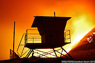 A lifeguard tower stands on the beach at Point Mugu State Park as the Springs Fire burns on the nearby hillside on May 3, 2013. A wind-driven wildfire raging along the California coast north of Los Angeles prompted the evacuation of hundreds of homes and a university campus on Thursday as flames engulfed several farm buildings and recreational vehicles near threatened neighborhoods. REUTERS/Jonathan Alcorn  (UNITED STATES)