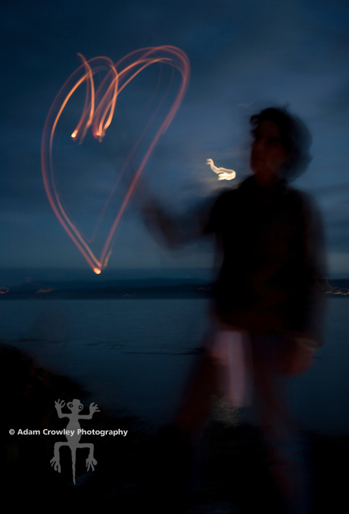Long exposure of a woman (40 years old) making shape of a heart w/a burning stick