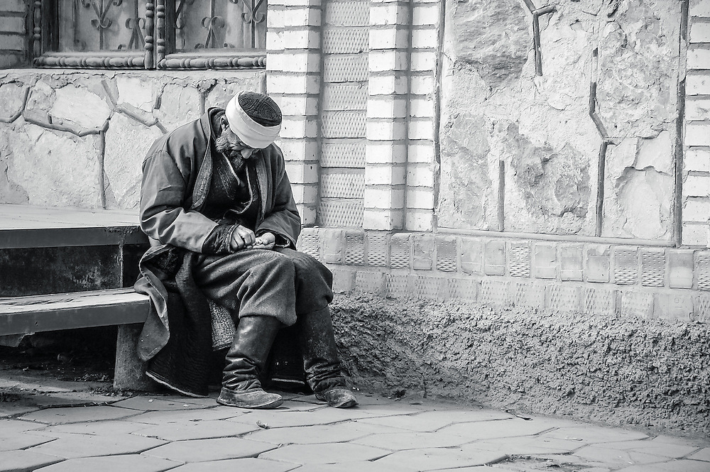 Portrait of an old Tajik man resting on a step and counting his coins in western Tajikistan