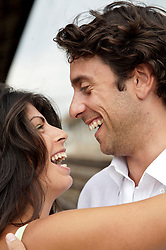 Close up of young couple laughing and emabracing