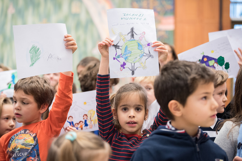 """21 November 2018, Geneva, Switzerland: Children from the Greek schools in Geneva and Lausanne hold up drawings to be given to the Ecumenical Patriarch Bartholomew as a gesture of welcome, as he arrives at the Ecumenical Centre. On the occasion of 2018 World Children's Day, and in recognition of the World Council of Churches' 70th anniversary, UNICEF and WCC convene a number of WCC member churches and common partners to celebrate the UNICEF-WCC global partnership and to take stock of the many achievements of the Churches' Commitments to Children. In line with the spirit of a day """"for children, by children,"""" the celebratory event placed children at the centre by asking them to share their recent experiences as participants in the several Youth Talks on ending violence in schools that WCC member churches around the world have organized in recent years; hearing the perspective of young migrants supported by a church-run sponsorship project; and showcasing promising examples of how churches support children in climate justice activities."""