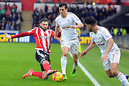 Southampton's Cedric Soares (l) tackles Swansea's Jack Cork (c). Barclays Premier league match, Swansea city v Southampton at the Liberty Stadium in Swansea, South Wales on Saturday 13th February 2016.<br /> pic by  Carl Robertson, Andrew Orchard sports photography.