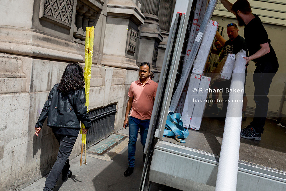 Carrying a yellow rolled-up protest banner, a lady walks down Bishopsgate and passes a delivery van with bubble-wrapped goods in the back, in the City of London, the capital's financial district, on 17th June 2019, in London, England.